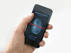 Hand holding smartphone with mobile security application 183611708