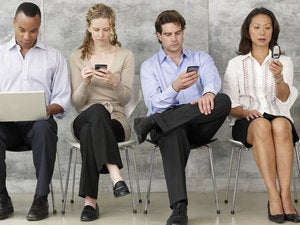 four professionals looking at mobile devices