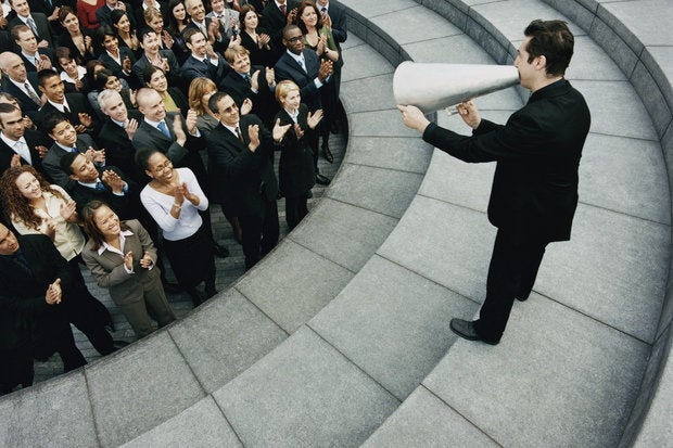 businessman standing on steps outside talking through a megaphone large group of business people li