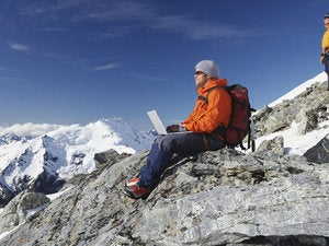 Man of mountain peak using wireless laptop in remote area