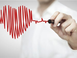 man holding pen drawing a heartbeat and red heart