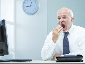 older executive sitting at laptop yawning