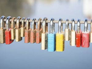 Row of colorful padlocks hanging on cable with water in background
