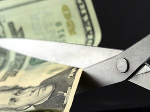 Scissors cutting money for budget slashing