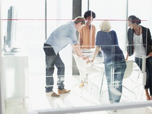 Group of people huddled around office table