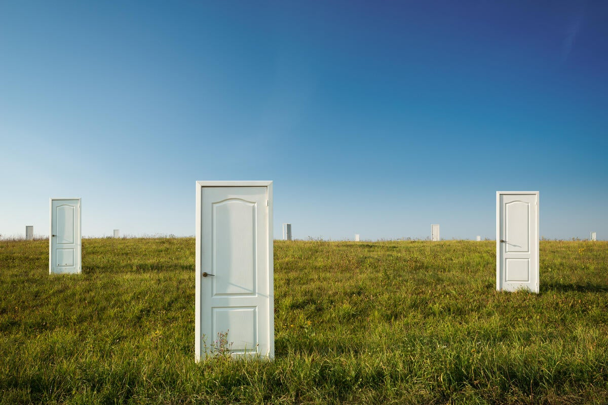 three lone doors in open grassy field