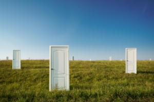 three lone doors in open grassy field